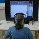 Eine Frau sitzt mit Kopfhörern vor PC