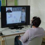 Ein Mann sitzt mit Headset vor Bildschirm