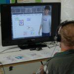 Ein Mann sitzt mit Headset vor einem Bildschirm