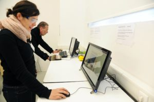 2 Menschen versuchen mit Handschuh und Milchglasbrille einen PC zu bedienen
