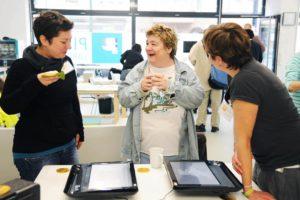 Besucher und Mitarbeiter vor Touchscreenmonitor