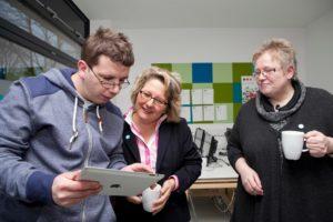 NRW-Forschungsministerin lässt sich von einem Benutzer etwas am Tablett zeigen