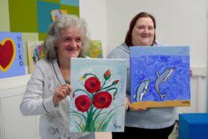Besucher präsentieren selbst gemalte Bilder