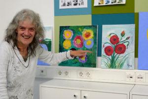 Frau zeigt ihre selbst gemalten Bilder