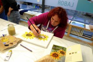 Besucherin malt Sonnenblumen